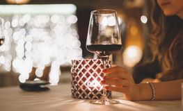 Woman hand holds a glass of wine in a restaurant with evening candle lighting royalty free stock images