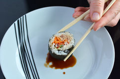 Woman hand holds one Makizushi sushi fresh maki roll with chopst Royalty Free Stock Photography