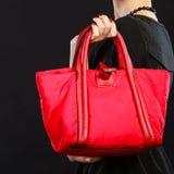 Woman hand holds red handbag Stock Image