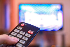 Woman hand holds remote control TV Stock Image