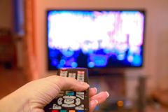 Woman hand holds remote control TV Royalty Free Stock Photography