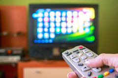 Woman hand holds remote control TV stock photography