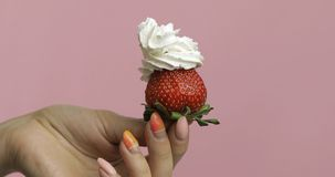 Woman hand holds strawberry with whipped cream on top of the berry stock photo