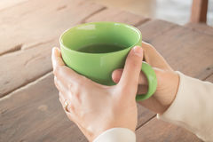 Woman hand on hot green tea drinking Stock Photography