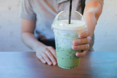 Woman Hand On Iced Milk Green Tea Drink Stock Photo