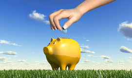 Woman hand inserting a coin into a piggy bank. Stock Photos