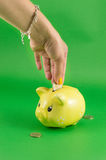 Woman hand inserting coin into piggy bank Royalty Free Stock Images
