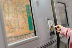 Woman hand inserts card to buy subway train ticket in machine. Transportation concept royalty free stock photos