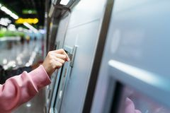 Woman hand inserts coin to buy subway train ticket in machine. Transportation concept royalty free stock photo