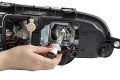Woman hand installing H7 led headlight bulb. With wires. Abstract: Modern car lighting technology Royalty Free Stock Photo