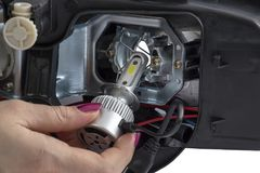 Woman hand installing led headlight bulb. With wires. Abstract: Modern car lighting technology Royalty Free Stock Images