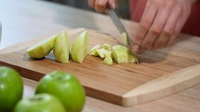 Woman hand with a knife cuts the apple on the wooden board in the kitchen. Healthy eating and lifestyle.  stock footage