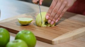 Woman hand with a knife cuts the apple on the wooden board in the kitchen. Healthy eating and lifestyle. Woman hand with a knife cuts the apple on the wooden stock video