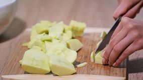Woman hand with a knife cuts the apple on the wooden board in the kitchen. Healthy eating and lifestyle. Woman hand with a knife cuts the apple on the wooden stock footage
