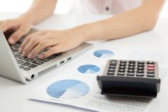 Woman hand on laptop with business report. And calculator Royalty Free Stock Image