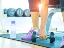 Woman hand lifting dumbbell in gymnasium. With fitness equipments in backgroound stock image