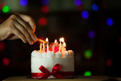Woman hand lighting candle on birthday cake Royalty Free Stock Photo