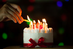 Woman hand lighting candle on birthday cake Stock Image