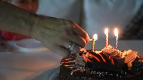 Woman hand lighting candles on chocolate cake. Woman hand lighting candles on birthday chocolate cake with match, video stock video footage