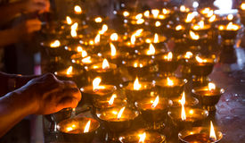 Woman hand lighting candles in a temple Royalty Free Stock Photo