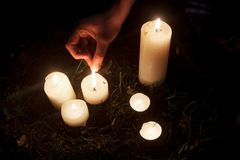 Woman hand lighting up candles at bridal shower in summer park,. Moment at party or birthday reception or mourning Stock Photos