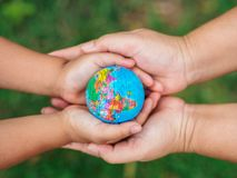 Woman hand and little giel haand holding the globe. Safe the Ear royalty free stock photo