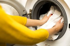 Woman hand loading dirty clothes in washing machine. Putting in Stock Photography