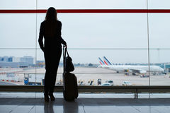 Woman with hand luggage in international airport, looking through the window at planes. Silhouette of a young elegant business woman with hand luggage in Stock Photography