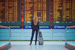 Woman with hand luggage in international airport terminal, looking at information board Stock Photos