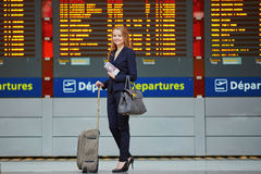 Woman with hand luggage in international airport terminal, looking at information board Royalty Free Stock Image