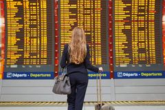 Woman with hand luggage in international airport terminal, looking at information board Royalty Free Stock Photo
