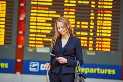 Woman with hand luggage in international airport terminal, looking at information board Royalty Free Stock Images