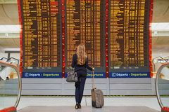 Woman with hand luggage in international airport terminal, looking at information board Stock Image