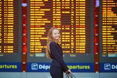 Woman with hand luggage in international airport terminal, looking at information board Royalty Free Stock Photography