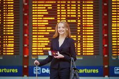 Woman with hand luggage in international airport terminal, looking at information board Royalty Free Stock Photos