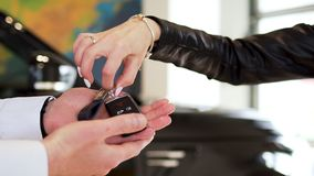 Woman hand with manicure, bracelet, and rings taking car keys from a man seller at the dealership. Stock. Salesman hand stock photography