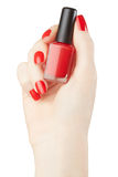 Woman hand manicure with red nail polish bottle Royalty Free Stock Image