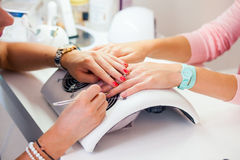 Woman hand on manicure treatment in beauty salon. Beauty parlour. Indoor photo Stock Photo