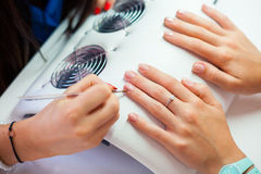 Woman hand on manicure treatment in beauty salon. Beauty parlour. Indoor photo Royalty Free Stock Photos