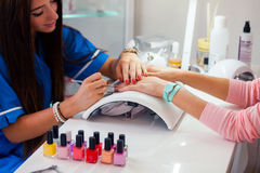 Woman hand on manicure treatment in beauty salon. Beauty parlour. Indoor photo stock image