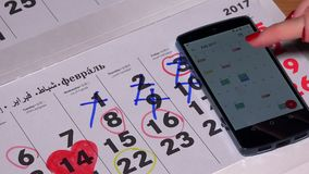 Woman hand with marker update paper calendar from her android device calendar. VILNIUS, LITHUANIA - NOVEMBER 30, 2016: Woman hand with marker update paper stock footage