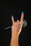 Woman hand with microphone and devil horns isolated on black Stock Photography