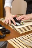 Woman hand moistening with water a sushi roll edge Royalty Free Stock Photography