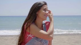 Woman with hand near hair blowing in the wind. Gorgeous young beautiful woman putting hand through long brown hair at windy sandy ocean beach with hand on neck stock video footage