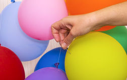 Woman hand with needle ready to pop a yellow balloon. There are some balloons around royalty free stock photos