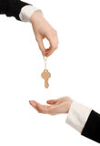 Woman hand offering a key. Woman hand receiving a key. Royalty Free Stock Photography