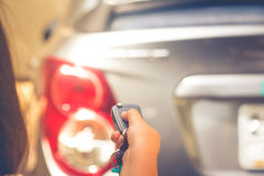 Woman hand open hers car with car remote key. Royalty Free Stock Photo