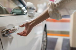 Woman hand opening car door inside a parking Royalty Free Stock Photos