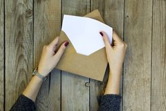 Woman hand opening envelope on wooden table. stock photo