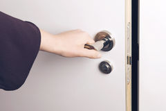 Woman hand opens a door to a dark and unknown room. Royalty Free Stock Photography